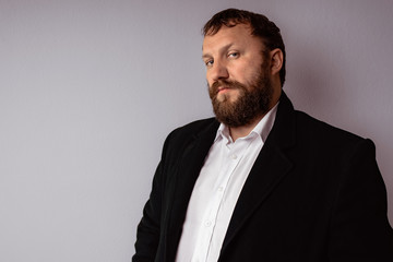 Handsome confident mature man with beard who wearing coat and shirt stands on gray background.