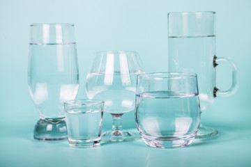 Transparent water in different glasses.