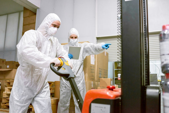 Concentrated young worker wearing coverall and safety mask using hand pallet truck while working in warehouse of pharmaceutical factory, his superior using digital tablet and guiding his actions