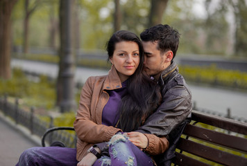 Young couple kissing on the bench in springtime
