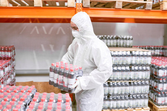 Profile view of male worker wearing coverall and safety mask carrying soft drink bottles in plastic wrap while focused on loading goods, interior of factory warehouse on background