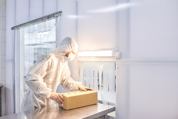 Male worker wearing coverall and safety mask standing at laboratory bench and packing pill bottles in cardboard box