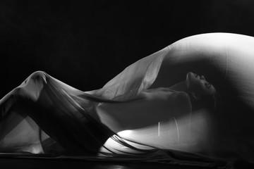 Fototapeta premium zmysłowy seksowny wygląd pięknej figury dziewczyny ukrytej w lekkiej cienkiej tkaninie, aby pokazać sylwetkę kobiecego ciała leżącego na podłodze
