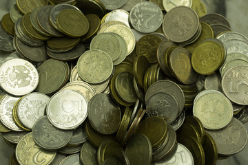 A pile of old coins from different currencies and materials .