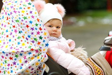 Cute little beautiful baby girl sitting in the pram or stroller on cold day