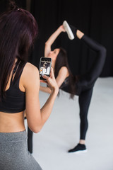 The back view of the sports woman taking photo of the blurred athletic girl in the pose of standing bow. The view of the girl friend on the phone.