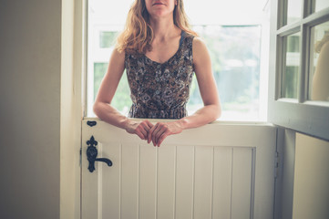 Young woman standing by stable door