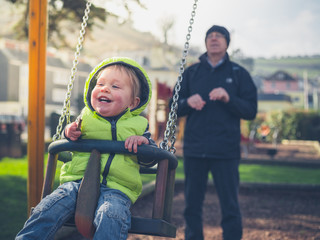Grandfather pushing grandchild on swing