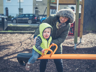 Grandmother playing with toddler on seesaw