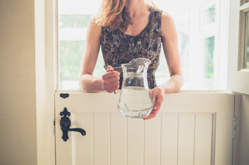 Woman with jug of water by stable door