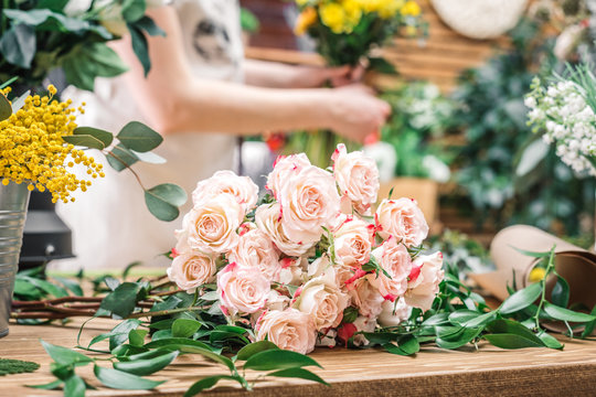 Beautiful pink roses and green branches on working counter in floral shop.