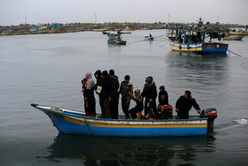 Palestinians ride a boat at the seaport of Gaza City