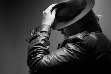 Caucasian Male in vintage trench coat and fedora. Black and white hand on hat