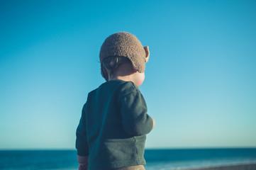 Little boy on the beach in winter