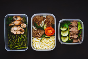 Photo sur Plexiglas Assortiment the healthy food in the containers on black background: snack, dinner, lunch. Baked fish, beans, beef cutlets, mashed potatoes, meat and vegetables