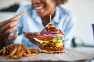 african american woman with vegan meatless burger meal