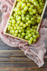 Photo from above of green grapes in wooden box with pink cloth