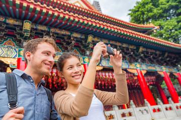 Wall Mural - Hong Kong tourists couple visiting attraction Wong Tai Sin Temple taking selfie photo picture at Hong Kong landmark. Asia China travel sightseeing Taoist temple. Asian woman, Caucasian man.