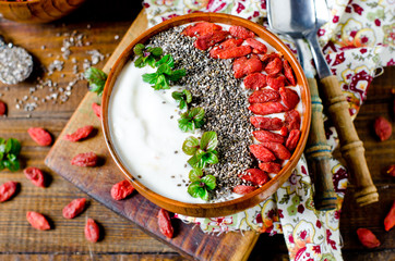 Healthy breakfast yogurt bowl with chia seeds, flax seeds, goji berries