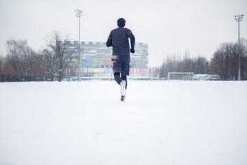 Photo of running athlete in black clothes on stadium