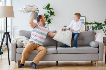 Photo of father fighting with son cushions on gray sofa