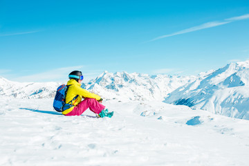 Photo of sports woman wearing helmet and mask sits on snowy slope