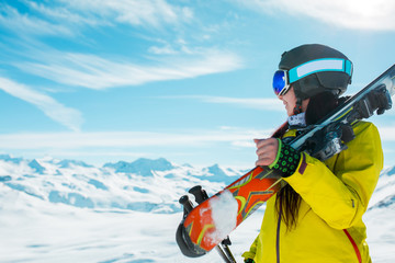 Photo of side view of sporty woman in helmet with skis on her shoulder against background of winter hills