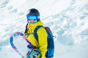 Picture of smiling woman in helmet and with snowboard on background of snowy landscape