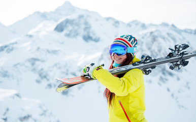 Photo of woman in mask with skis on her shoulder standing sideways