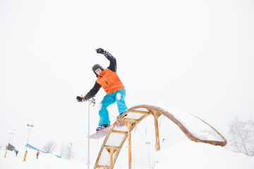 Picture of young sportive man skiing on snowboard with springboard