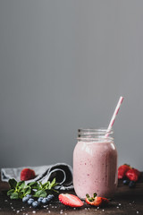 Pink strawbery smoothie in jar with drinking straw on grey background with copy space for text