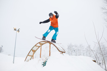 Photo of athlete skating on snowboard with springboard against background of trees