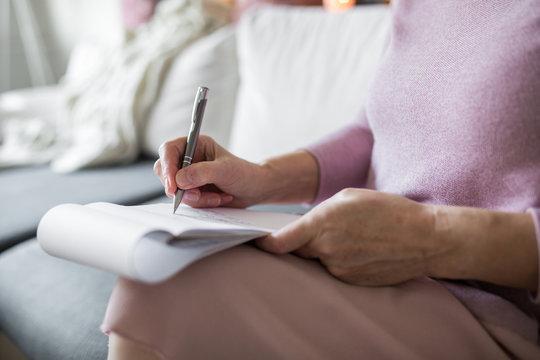 Senior lady holding notepad taking notes