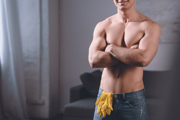 cropped image of seductive shirtless man standing with crossed arms, rubber gloves in jeans