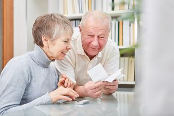 Paar Senioren mit Taschenrechner und Kassenzettel