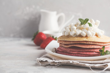 Stack of pink ombre  pancakes with marshmallow and strawberries. Breakfast background, copy space.