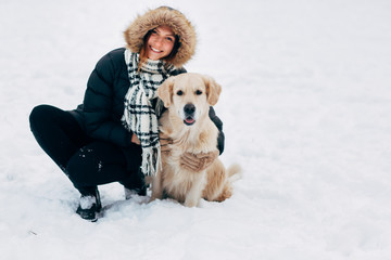Picture of smiling woman with labrador in winter park