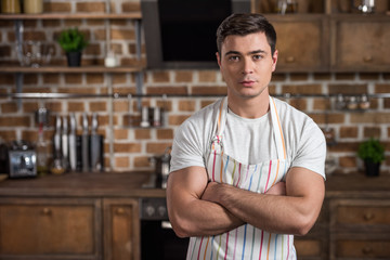 handsome man standing with crossed arms in apron at kitchen