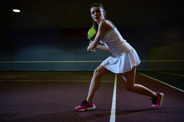 Full length motivational portrait of beautiful young woman playing tennis in dark indoor court swinging racket to hit ball, copy space