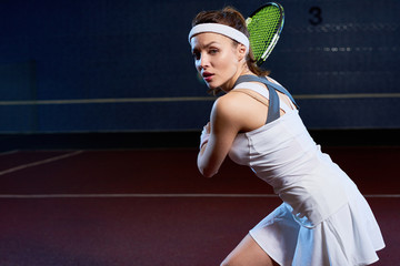 Waist up portrait of confident young woman playing tennis in dark indoor court, forcefully hitting ball with racket, copy space