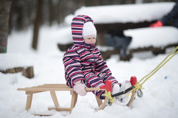 Two year old girl wearing striped coverall snow suit riding sleds in the snow.