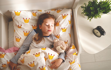 child  girl sleeps in her bed with toy teddy bear  in morning