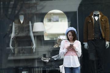 休日に街へ買い物に来た女子大学生はショーウィンドウの前でスマートフォンを使う。