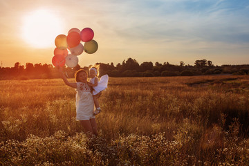 happy mother and daughter with balloons at sunset