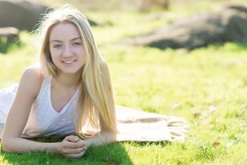teen girl  lays on the grass. Sunbeams