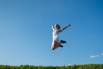 full lenth portrait of young woman is jumping on the meadow