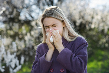 Girl blows his nose in a handkerchief against a backdrop of a blooming garden. The concept of an allergy