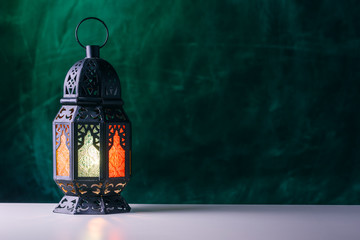 Holy month of Ramadan concept. Burming, lighting, glowing Ramadan Lantern on white table on the background of a dark green textured wall. Place for text on the right