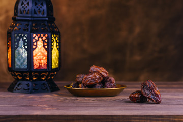 Holy Ramadan concept. Dates close-up in the foreground. On the distant plan a slightly blurry Ramadan Lantern on a wooden table. Textured yellow wall background. Space for text on the right.