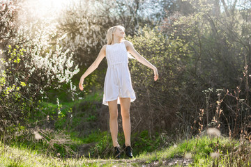 Teenage girl in white dress is jumping in the spring garden